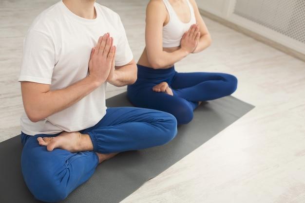 Nicht erkennbares paar, das yoga praktiziert, das in padmasana sitzt. junger mann und frau im lotussitz machen atemübungen auf der matte im sportclub-interieur, kopierraum