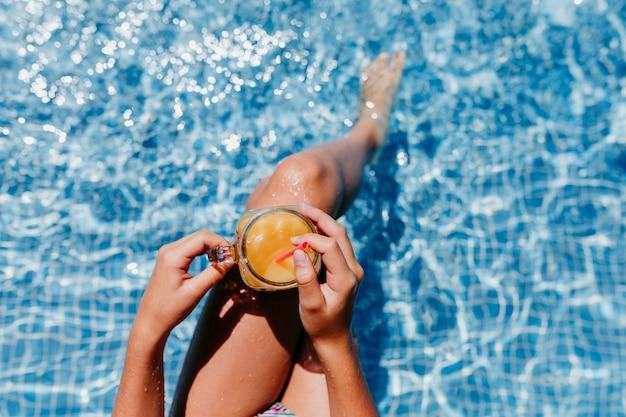 Nicht erkennbares teenager-mädchen am pool, das gesunden orangensaft trinkt und spaß im freien hat. sommer- und lifestyle-konzept