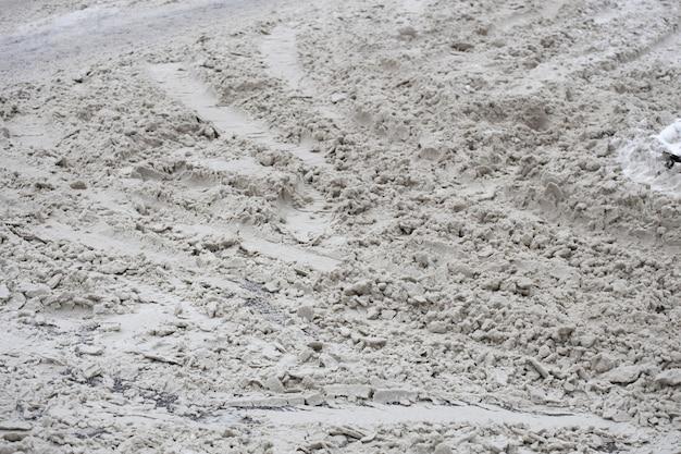 Nicht gereinigter schnee auf der straße der stadt mit spuren von autos. foto in hoher qualität