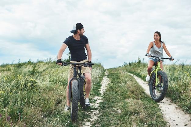 Nicht hinterherfallen der junge mann auf dem fahrrad überholt die attraktive frau Premium Fotos