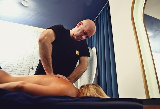 Nicht identifizierte frau, die eine professionelle therapeutische körpermassage im wellness-spa-center erhält