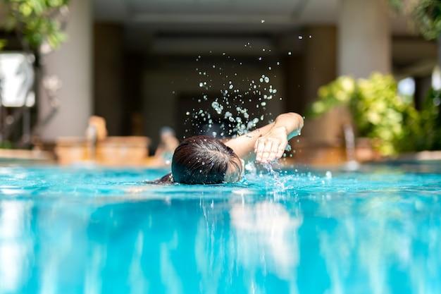 Nicht identifizierte frau, die im urlaub vordere schleichenschwimmen im swimmingpool tut.