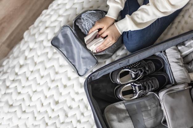 Nicht identifizierte frau legt dessous in den reiseaufbewahrungsbehälter