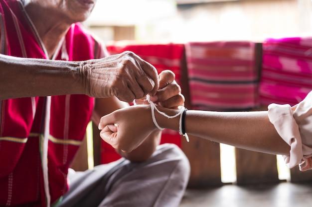 Nicht identifizierter älterer mann von der ethnischen bergvolk-minderheit der karen bindet das handgelenk des gastes für den segen in der bindezeremonie