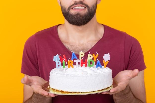 Nicht identifizierter junger männlicher hipster mit einem bart, der einen kuchen mit der aufschrift alles gute zum geburtstag glückwünsche zum jahrestag und zum feiertag hält. konzept von aktionen und rabatten.