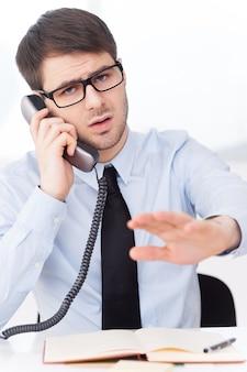 Nicht jetzt! wütender junger mann in hemd und krawatte, der am handy spricht und gestikuliert, während er an seinem arbeitsplatz sitzt