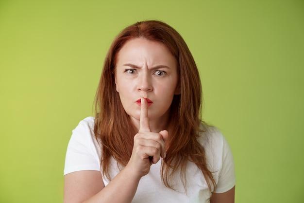 Nicht sprechen während der prüfung streng ernsthaft aussehende unzufriedene mittelgroße rothaarige frau runzeln die stirn enttäuscht enttäuscht schweigen sagen shush zeigefinger gedrückt lippen halten leise geste grüne wand