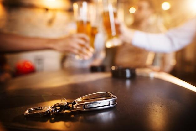 Nicht trinken und fahren! autoschlüssel auf einem hölzernen kneipentisch vor dem verschwommenen freund, der mit einem bier klirrt.
