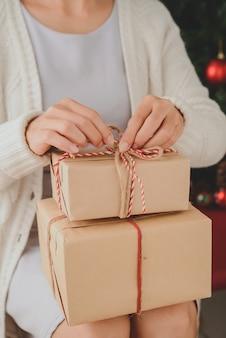 Nicht wiedererkennbare frau, die mit eingewickelten geschenken auf schoss sitzt und bogen löst