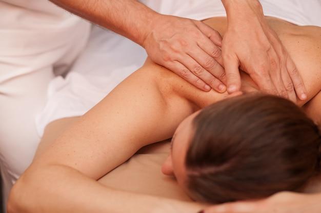 Nicht wiedererkennbare frau, die rückenmassage von einem professionellen masseur in der schönheitsklinik erhält. badekurorttherapeut, der zurück vom weiblichen kunden massiert. frau, die therapeutische körpermassage genießt. hautpflege, gesundheit