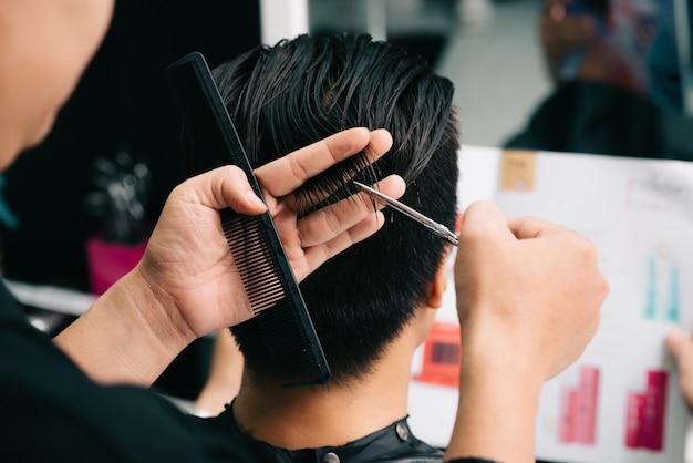 Nicht wiedererkennbarer friseur, der das haar des kunden mit kamm und scheren im salon schneidet