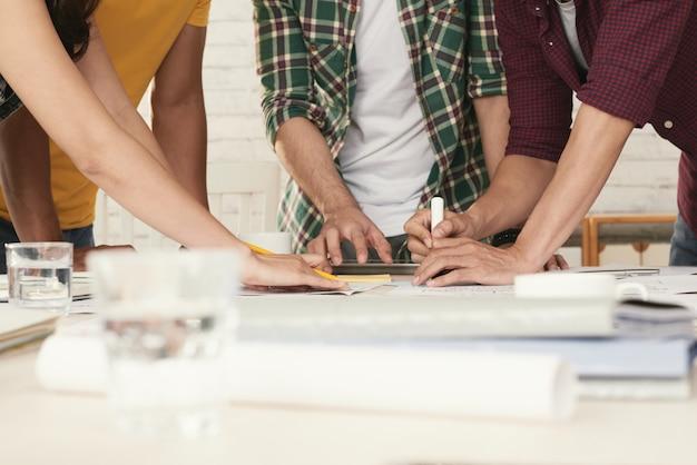 Nicht wiederzuerkennende beiläufig gekleidete leute, die um den tisch stehen und brainstorming betreiben