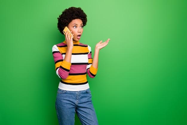 Nicht zu glauben! von ziemlich geschockter dunkler haut gewellte dame, die telefon spricht bester freund hört schreckliche schlechte nachrichten tragen lässig gestreifte pulloverjeans