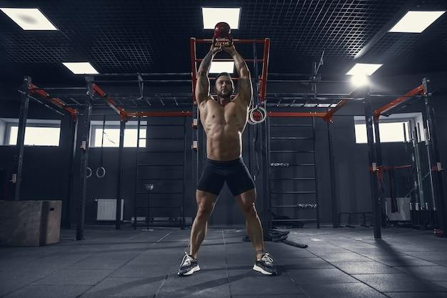Nicht zu stoppen. junger muskulöser kaukasischer athlet, der kniebeugen im fitnessstudio mit dem gewicht übt. männliches model macht kraftübungen und trainiert den unterkörper. wellness, gesunder lebensstil, bodybuilding-konzept.