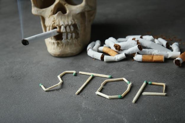 Nichtraucherkonzept. wort stop aus zigaretten und totenkopf auf grauem hintergrund