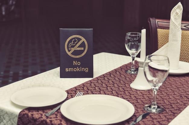Nichtraucherseufzer auf tisch mit gläsern, serviette und tellern im restaurant