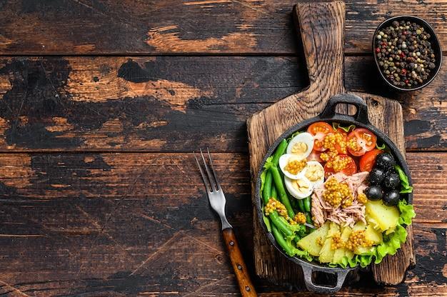 Nicoise-salat mit thunfisch, kirschtomaten, oliven, grünen bohnen, gurke, weich gekochten eiern und kartoffeln