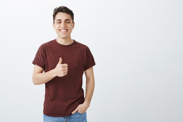 Nie besser witz gehört. glücklicher schöner mann im lässigen roten t-shirt mit dem daumen nach oben