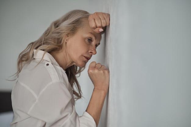 Niedergeschlagene reife blonde frau, die unter einsamkeit leidet