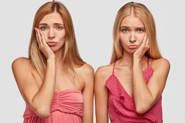 Niedergeschlagene traurige blonde schwestern oder beste begleiter runzeln die stirn und halten die hände auf den wangen, schlecht gelaunt
