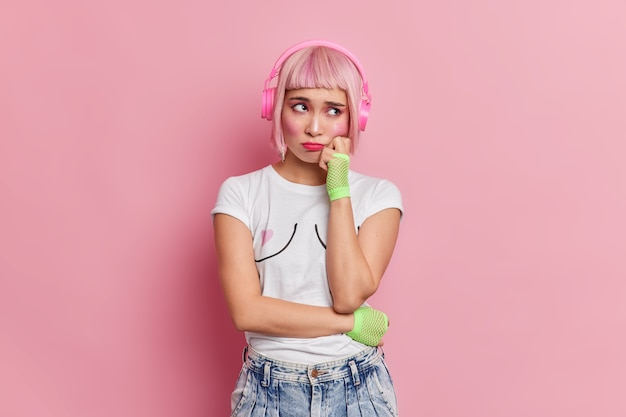 Niedergeschlagene unzufriedene asiatin hat einen unglücklichen ausdruck hält die hand auf der wange trägt ein lässiges t-shirt jeans hört musik über drahtlose kopfhörer, die verärgert sind, um einen unglücklichen tag zu haben