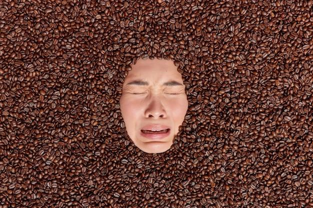 Niedergeschlagene verärgerte frau weint aus verzweiflung steckt den kopf durch kaffeebohnen