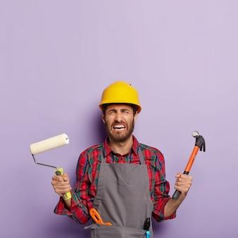 Niedergeschlagener weinender vorarbeiter, der die jährliche arbeit satt hat, bauwerkzeuge in der hand hält, verzweifelt aussieht, eine freizeituniform trägt und mit reparaturen beschäftigt ist. verzweifelter vorarbeiter mit farbroller und hammer