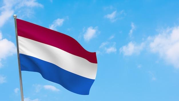 Niederländische flagge auf der pole. blauer himmel. nationalflagge der niederlande