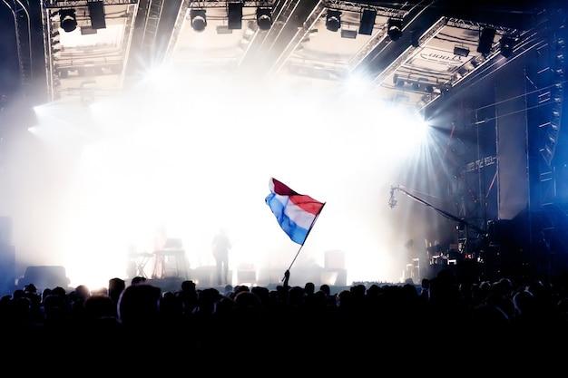 Niederländische flagge beim konzert gegenüber dem licht von der bühne