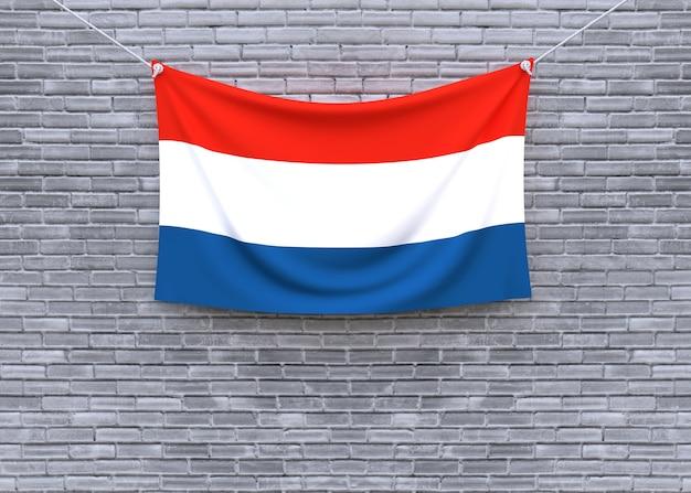 Niederländische flagge, die an der backsteinmauer hängt