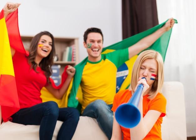 Niederländische frau, die durch vuvuzela während des fußballspiels bläst