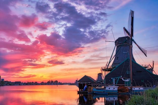 Niederländische ländliche szene - windmühlen am berühmten touristenort zaanse schans in holland auf sonnenuntergang mit dramatischem himmel. zaandam, niederlande