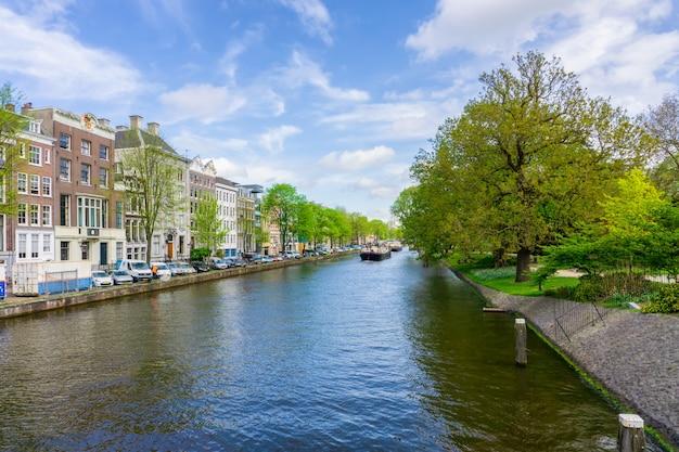 Niederländische tanzenhäuser amsterdams über fluss amstel-markstein in der alten europäischen stadtfrühlingslandschaft