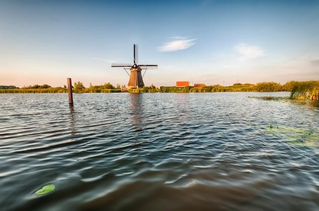 Niederländische windmühle in der nähe des flusses