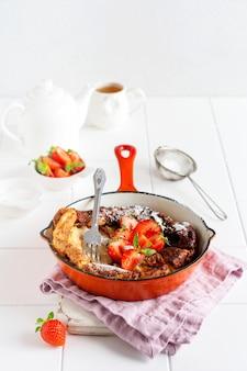 Niederländischer babypfannkuchen mit frischer erdbeerbeere und mit puderzuckerpulver in roter pfanne auf weißer küchenoberfläche bestreut. draufsicht.