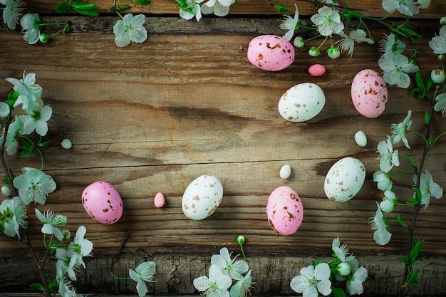 Niederlassung von frühlingsblumen und von bunten rosa süßigkeitseiern für ostern auf rustikalem