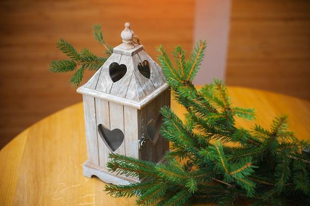 Niederlassung von weihnachtsbäumen und von weißem hölzernem kerzenständer auf dem tisch