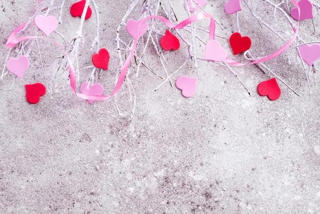 Niederlassungen im schnee mit den rosa und roten herzen auf einem konkreten hintergrund