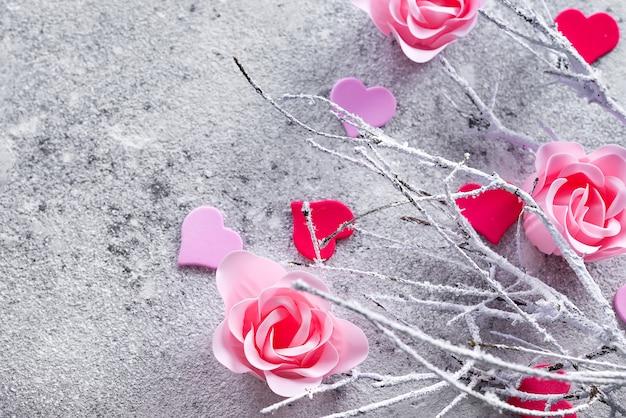 Niederlassungen im schnee mit den rosafarbenen rosafarbenen knospen und den herzen auf einem konkreten hintergrund