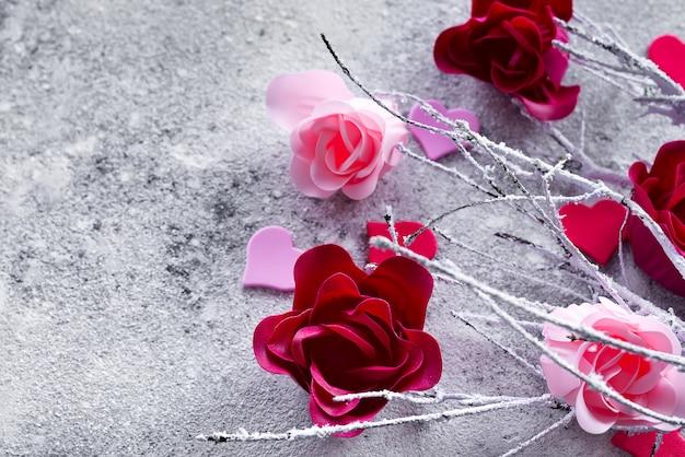 Niederlassungen im schnee mit den rosafarbenen und roten rosenknospen und den herzen auf einem konkreten hintergrund