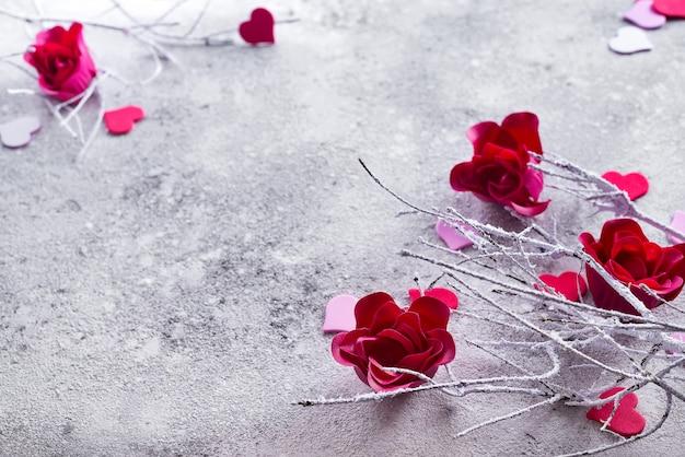 Niederlassungen im schnee mit den roten rosenknospen und den herzen auf einem konkreten hintergrund
