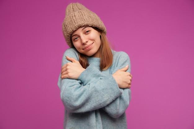 Niedlich aussehende frau, schönes mädchen mit brünetten haaren. trägt einen blauen pullover und eine strickmütze.