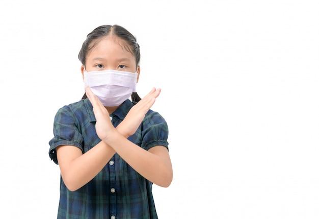 Niedliche asiatische tragen chirurgische maske zum schutz vor covid-19-viren und zeigen handbewegung zum stoppen.