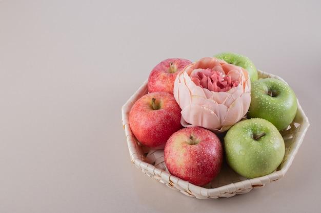 Niedliche box mit äpfeln auf weißer oberfläche.