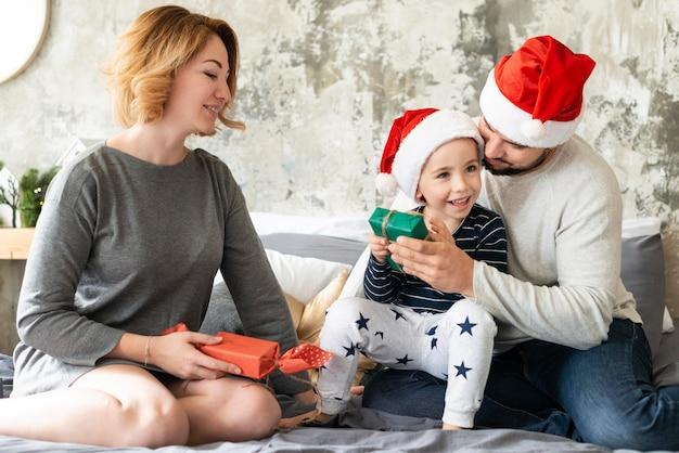 Niedliche familie der vorderansicht, die zusammen am weihnachtstag ist