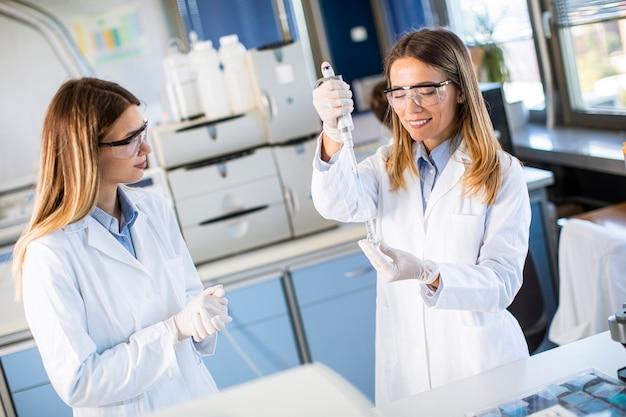 Niedliche forscherinnen im weißen laborkittel, die im labor arbeiten