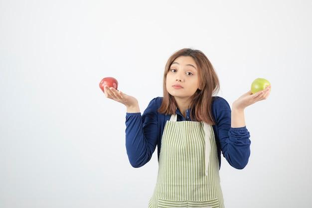 Niedliche junge frau modell in schürze hält äpfel.