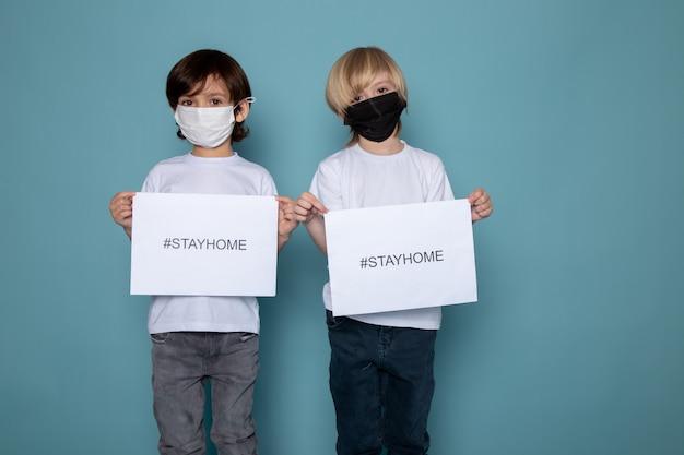 Niedliche jungen kleine süße mit zu hause bleiben hashtags gegen coronavirus in weißen t-shirts und jeans an der blauen wand
