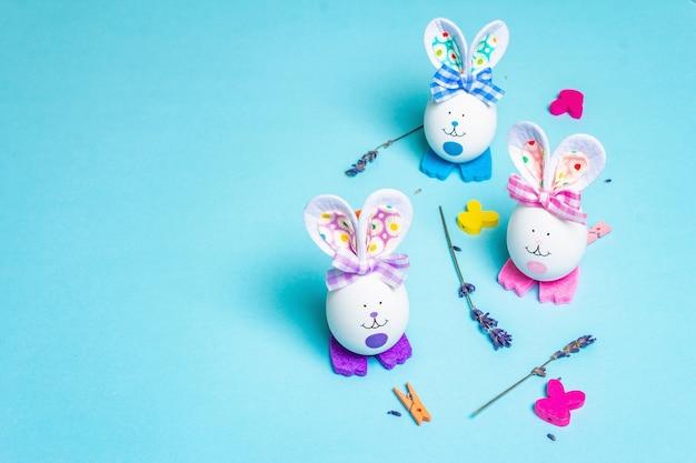 Niedliche kaninchen aus eiern, duftenden lavendelzweigen und festlichem dekor