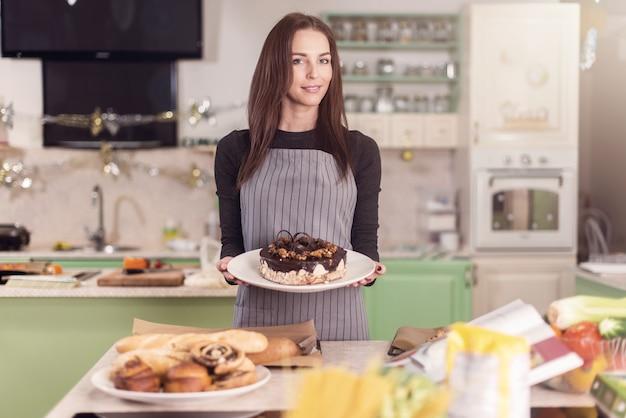Niedliche kaukasische bäckerin, die kuchen, kekse und anderes gebäck zeigt, das in der bäckerei gemacht wird